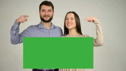 Happy couple standing together and pointing on green screen