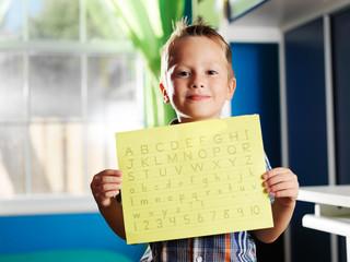 little boy holding completed homework