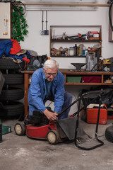 Senior worker with lawn mower in workshop