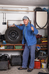 Senior worker with a tire in garage