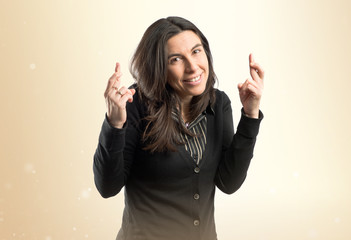 Adult girl crossing his fingers over white background