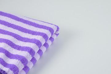Part of purple  bath-towel on table