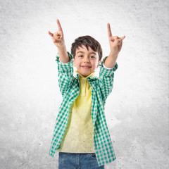 Kid doing the horn sign over white background