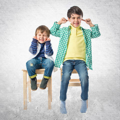 Boys covering his ears over white background.