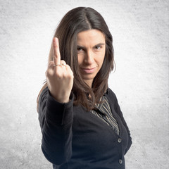 Adult girl making horn gesture over white background