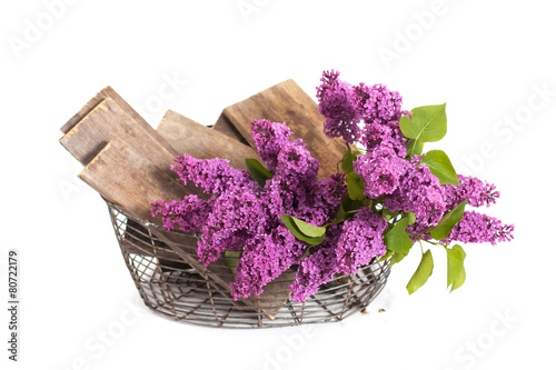 Foto op Canvas Lilac summer lilac flowers in basket on a white background