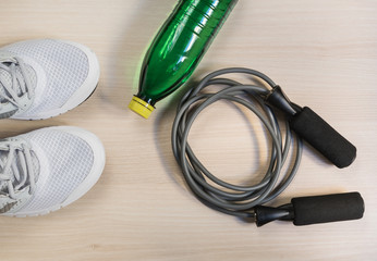 Skipping rope with sport shoes and bottle of water on wooden