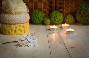 Flower on foreground, sponges, candles and rattan balls behind