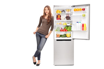 Casual young girl leaning on an opened refrigerator