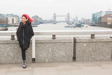 Beautiful woman listening music in London