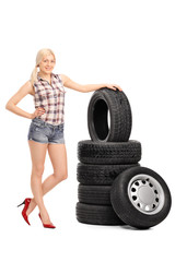 Attractive female worker standing by a stack of tires