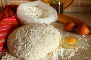Yeast dough, eggs, and flour on the table.