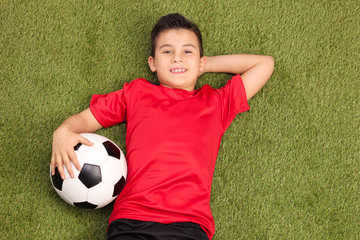 Relaxed youngster lying on pitch and holding a football