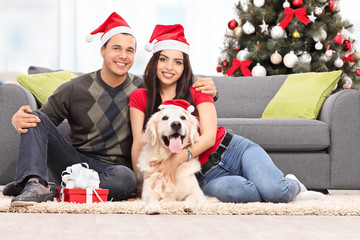 Couple celebrating Christmas together with their dog