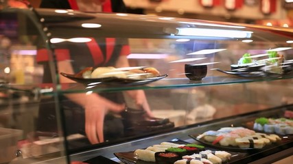 chef puts the dishes for sale in Japanese shop with sushi. Close
