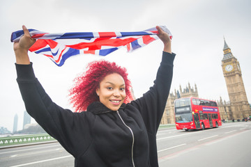 Beautiful redhair woman holding United Kingdom flag in London