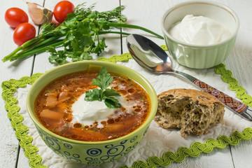 Borsch, sour cream and fresh vegetables