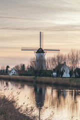 Windmill reflected in a canal at sunset