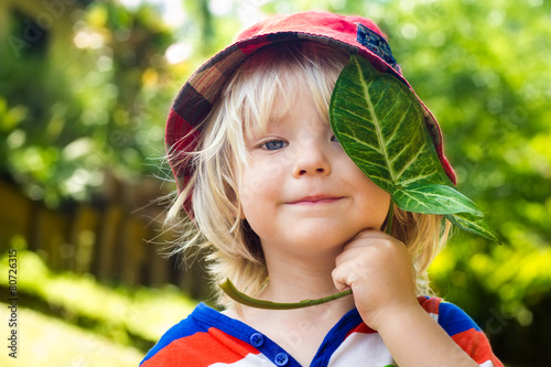 Cute happy child holding a leaf over his eye - 80726315