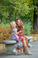 Happy mother and baby girl having fun time in city park