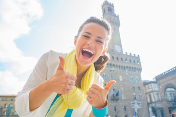 Happy young woman showing thumbs up in front of palazzo vecchio