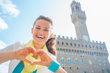 Happy woman showing heart gesture shaped hands  in florence