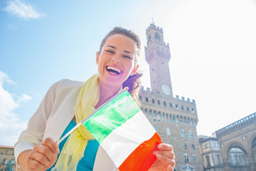 Happy young woman showing flag in front of palazzo vecchio