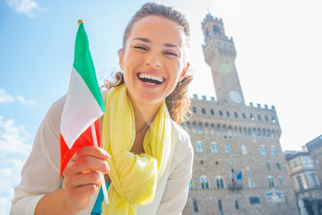 Happy woman with flag in front of palazzo vecchio  in florence