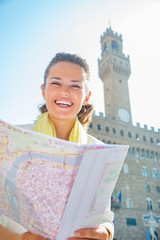 Happy young woman with map in front of palazzo vecchio