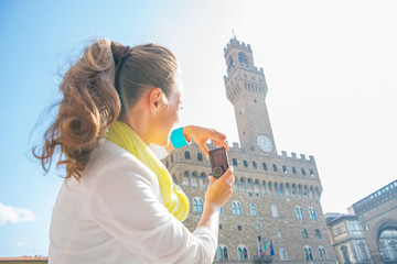 Young woman taking photo of palazzo vecchio in florence, italy