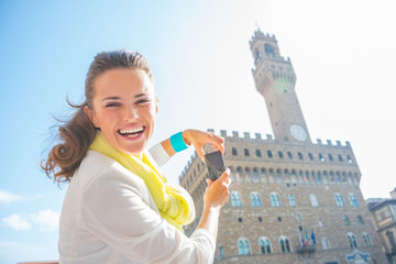 Happy young woman taking photo of palazzo vecchio in florence