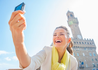 Happy young woman making selfie in front of palazzo vecchio