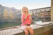 Happy baby girl eating ice cream near ponte vecchio in florence