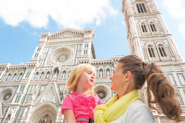 Happy mother and baby girl in front of duomo in florence, italy