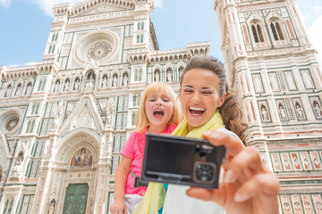 Smiling mother and baby girl making selfie in florence