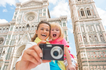 Happy mother and baby girl taking photo in florence