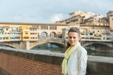 Young woman on embankment near ponte vecchio in florence, italy