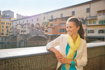 Happy young woman looking into distance near ponte vecchio