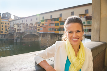 Portrait of smiling young woman near ponte vecchio in florence