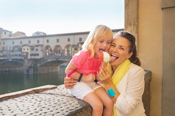Happy mother and baby girl eating ice cream near ponte vecchio
