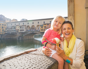 Mother and baby girl eating ice cream near ponte vecchio