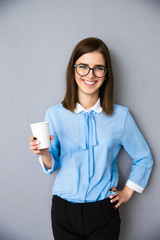 Happy businesswoman holding cup with coffee