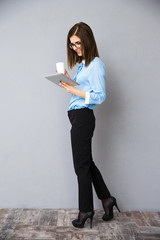 Businesswoman walking with cup of coffee and tablet computer
