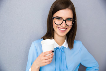 Smiling businesswoman holding cup with coffee