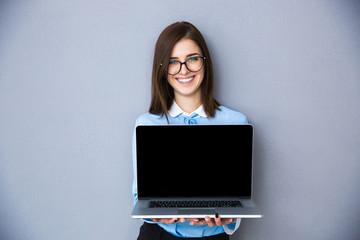 Happy businesswoman showing blank laptop screen