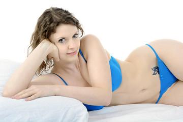 Frau in Unterwäsche liegt im Bett