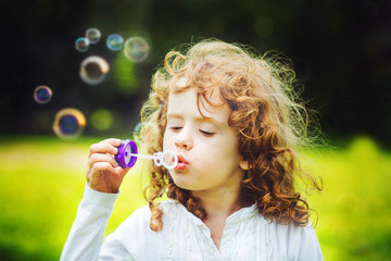 Girl blowing soap bubbles, closeup portrait beautiful curly baby