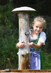 Little girl  wearing a traditional dress drinks water