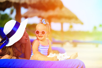 mother and cute little daughter having fun on summer beach