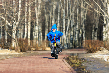 little boy enjoying bike ride in spring